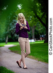 Woman Using Cell Phone in Park - Woman standing in park...