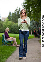 Woman Reading Text Message In Park