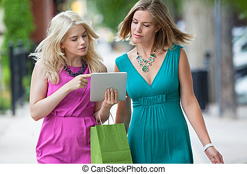 Female Friends Using Digital Tablet - Young women with...