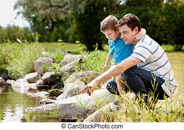 Fashing and Son Playing Near Lake - Father and son playing...