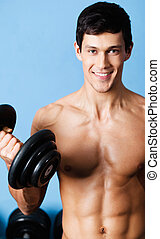 Muscular man uses his dumbbell - Handsome muscular man with...