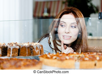 Lady in scarf looking at the bakery window