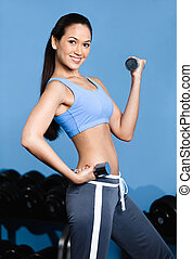 Athlete woman exercises with dumbbells