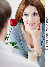 Woman at the cafe with red rose and her boyfriend