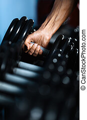 Hand taking out a dumbbell - Hand of a man taking a dumbbell...