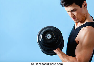 Handsome muscular man uses his dumbbell to exercise flexing...