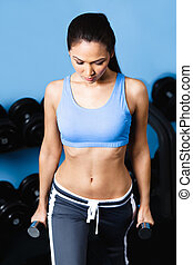 Athletic woman works out with dumbbells