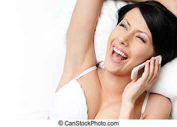 Woman in underwear speaks on phone while lying in the bed,...