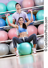Sportive woman exercises in fitness gym with couch