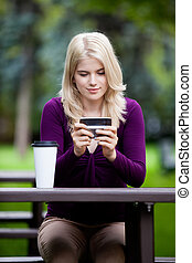Woman in Park using Cell Phone - Happy blond woman sitting...