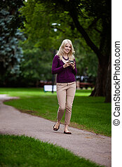 Woman Writing Text Message - Woman in park looking at camera...