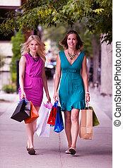 Two Women Walking Down Street - Two women with shopping bags...