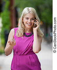 Woman Using Cell Phone in City - Beautiful young woman using...