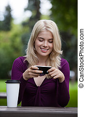 Woman Updating Status on Mobile Phone - Happy smiling young...