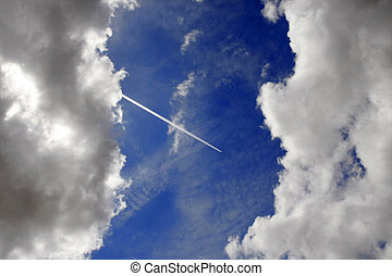 Passenger jet trails between two clouds