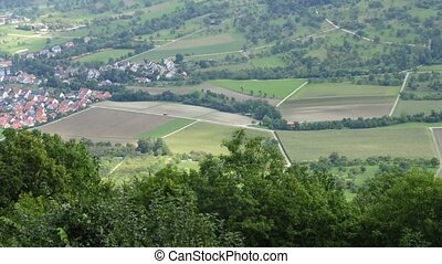 a bird eye`s view to green land with fields and pastures in...