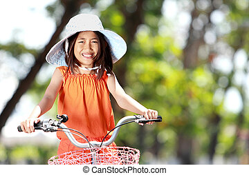 girl riding bicycle outdoor - portrait of smiling litte girl...