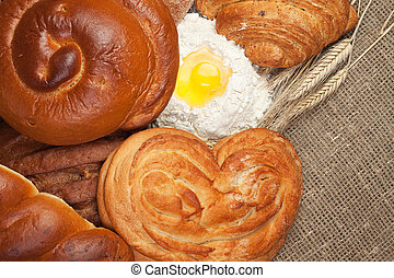 variety of fresh bread with ears of rye and flour background