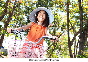 girl riding bicycle outdoor - happy attractive litte girl...