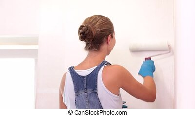 Painting walls white. - Young girl paints the wall white and...