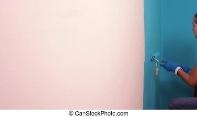 Painting Walls blue. - Young girl paints the wall blue and...
