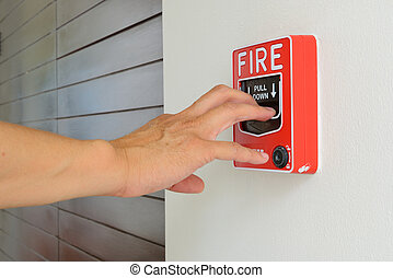 The hand of man is pulling fire alarm on the wall next to...