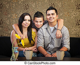 Happy Hispanic Family - Young smiling Latino family sitting...