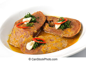 Stewed slices of beef tongue with sauce and seasoning on a...