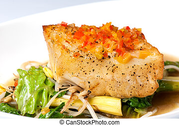 Baked fish - Baked halibut with vegetable garnish on a white...