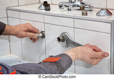 Plumbing - Plumber hands fixing water pipe with spanner and...