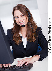 Smiling receptionist or call centre worker sitting typing at...