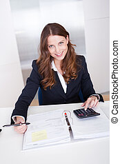Businesswoman using a calculator - Smiling stylish...