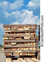 Lumber industry, heap of wooden beams with sky in background