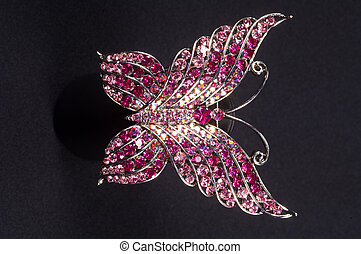 brooch in the shape of a butterfly on a black background...