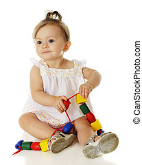 Baby Bead Play - An adorable baby girl happily playing with...