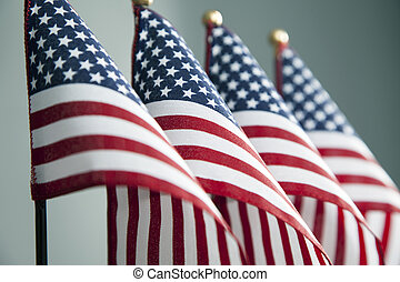 Four Flags - Four American flags stand in a row.