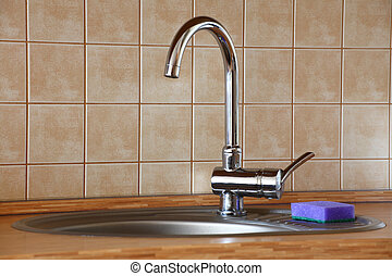 chrome water faucet in a wooden kitchen indoor