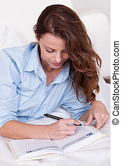 Woman writing in her diary - Attractive you woman lying...
