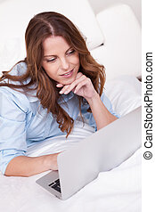 Woman relaxing on her bed with laptop