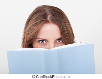 Young woman reading a book - Pretty young woman sitting on a...