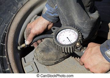 Tire servicing - Checking the air pressure in a tire with a...