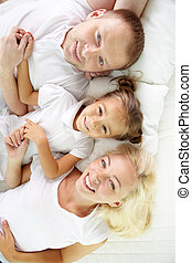 Lying on bed - Above angle of happy parents and daughter...