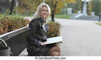 Autumn park visitor - Young woman sitting on a park bench...