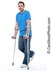 Young man with crutches trying to walk