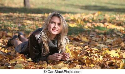 Girl at leisure - Pretty blonde lying on the fallen leaves...