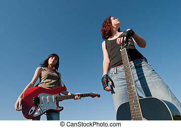 Teenage music - Two young girls with guitars over blue sky
