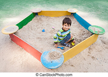 boy playing in sandbox - Cute boy playing in sandbox with a...