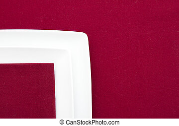 Two white square plates on red tablecloth