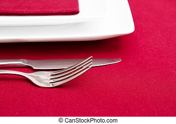 Cutlery and white squre plates on red tablecloth