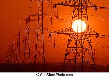 power sun - Setting Sun seen through a row of electricity...